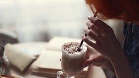 Het boek van de vrouwenlezing en het drinken koffie bij koffie stock videobeelden