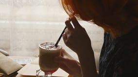 Het boek van de vrouwenlezing en het drinken koffie bij koffie stock video