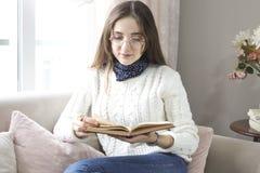 Het boek van de vrouwenlezing met kop van koffie thuis in de woonkamer royalty-vrije stock afbeeldingen