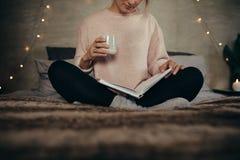 Het boek van de vrouwenlezing op bed thuis Stock Foto's