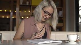 Het boek van de vrouwenlezing terwijl het drinken van koffie stock footage