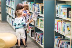 Het Boek van leraarswith children selecting in Bibliotheek royalty-vrije stock afbeelding