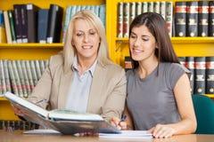 Het Boek van studentenand teacher reading samen bij Lijst royalty-vrije stock foto's