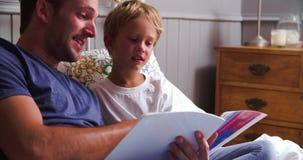 Het Boek van vaderand son reading in Bed samen stock videobeelden
