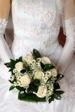 Het boeket van de bruid op de achtergrond van de kleding Royalty-vrije Stock Afbeeldingen