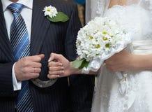 Het boeket van de bruidegom en van de bruid met een hoef in handen Stock Afbeelding