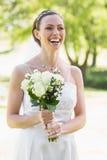 Het boeket van de bruidholding terwijl het lachen in tuin Royalty-vrije Stock Foto's