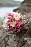 Het boeket van de huwelijksbruid van roze en witte bloemenrozen ligt op een logboek door het meer huwelijksachtergrond met exempl stock afbeelding