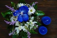 Het boeket van de lente bloeit en blauwe kaarsen met de hand gemaakt op een houten achtergrond, concept feestelijke samenstelling Stock Foto's