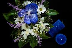 Het boeket van de lente bloeit en blauwe met de hand gemaakte kaarsen op een zwarte achtergrond, concept feestelijke samenstellin Royalty-vrije Stock Fotografie