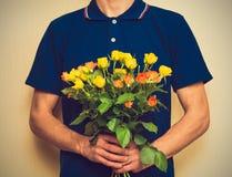 Het boeket van de mensenholding van gele en oranje rozen Womens dag, Va royalty-vrije stock afbeelding