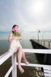 Het boeket van de vrouwenholding van bloemen die op pijler zitten Stock Foto