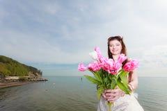 Het boeket van de vrouwenholding van bloemen op kust Stock Afbeelding