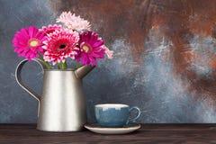 Het boeket van Gerberabloemen en koffiekop Stock Afbeelding