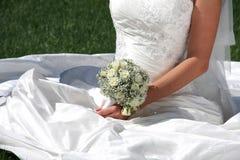 Het boeket van het huwelijk bij de handen van de bruid stock fotografie