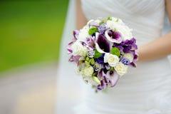 Het boeket van het huwelijk bij de handen van de bruid Royalty-vrije Stock Fotografie