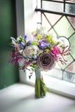 Het boeket van het huwelijk dichtbij een venster Stock Fotografie