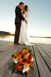 Het boeket van het huwelijk in voorgrond en jonggehuwden erachter Royalty-vrije Stock Afbeeldingen