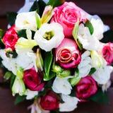 Het boeket van huwelijksbloemen met huwelijks gouden ringen Stock Foto's