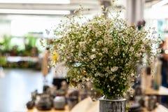 Het boeket van kleine witte bloemen in één of andere vaas blijft in grote binnenlandse ruimte met onduidelijke onderwerpen op ons stock foto