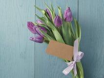 Het boeket van purpere tulpen bond met lint op blauwe houten lijst met document kaart Royalty-vrije Stock Afbeeldingen