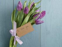 Het boeket van purpere tulpen bond met lint op blauwe houten lijst met document kaart i liefde u Stock Foto