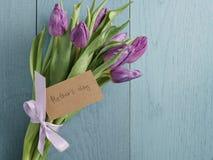 Het boeket van purpere tulpen bond met lint op blauwe houten lijst met document kaart voor moedersdag Royalty-vrije Stock Foto