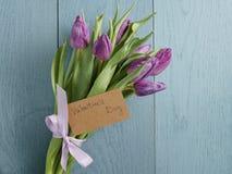 Het boeket van purpere tulpen bond met lint op blauwe houten lijst met document kaart voor valentijnskaartendag Stock Foto's