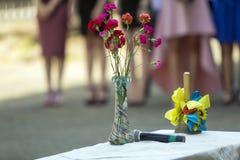 Het boeket van roze en rode bloemen, microfoon en verfraaid met blauwe en gele lintenklok op vage mensen silhouetteert zonnige ba royalty-vrije stock foto