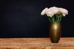 Het boeket van roze gevoelige boterbloemen van bloemen bevindt zich op een houten lijst in een gouden vaas royalty-vrije stock foto's