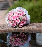 Het boeket van rozen ligt op de rand van de fontein royalty-vrije stock afbeeldingen