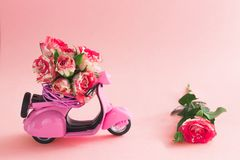 Het boeket van rozenbloem in mand op achterbank van leuke roze autoped en groot nam op roze achtergrond toe royalty-vrije stock afbeelding