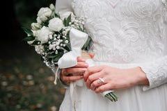 Het boeket van het schoonheidshuwelijk van roze bloemen en eucalyptustakken in de handen van de bruid stock foto's