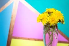 Het boeket van taraxacumpaardebloem bloeit in een glasvaas op een kleurrijke achtergrond De ruimte van het exemplaar stock fotografie
