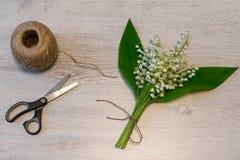 Het boeket van verse lelietje-van-dalen bloeit met streng van streng en schaar op lichte houten achtergrond Mooie de lentelay-out royalty-vrije stock fotografie