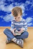 Het boekplaatsing van de jongenslezing op de vloer met wolk Stock Foto's