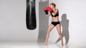 Het boksermeisje maakt tot slagen een ponsenzak met al hartstocht stock footage