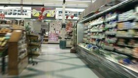 Het boodschappenwagentje die door kruidenierswinkeldoorgangen op tijd rennen verstrijkt stock video
