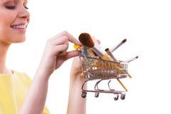 Het boodschappenwagentje van de vrouwenholding met maakt omhoog borstels Stock Afbeelding