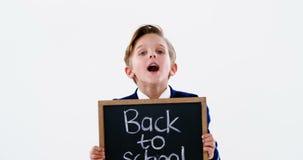 Het bord van de schooljongenholding met terug naar schooltekst stock videobeelden