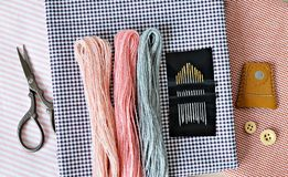 Het borduurwerkdraden van de pastelkleurwol, naalden, katoenen stof, retro schaar, houten knopen en leervingerhoedje royalty-vrije stock afbeeldingen