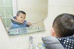Het borstelen van de jongen tanden Stock Fotografie