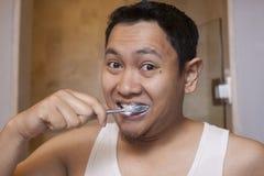 Het borstelen van de mens tanden in badkamers stock foto's