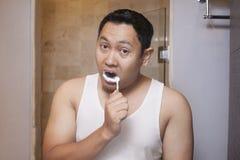 Het borstelen van de mens tanden in badkamers stock foto