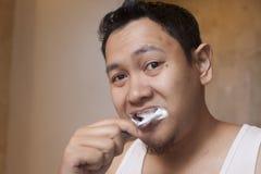 Het borstelen van de mens tanden in badkamers stock afbeelding