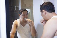 Het borstelen van de mens tanden in badkamers stock afbeeldingen