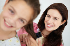 Het borstelen van de moeder het haar van de dochter Royalty-vrije Stock Afbeeldingen