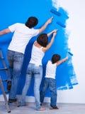 Het borstelen van de muur door familie Stock Foto's