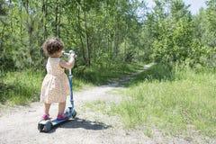 In het bos van de de zomerberk weinig krullend meisje die een autoped berijden Stock Afbeelding