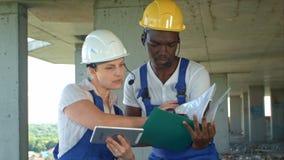Het bouwteam raadpleegt en bespreekt plannen voor de bouw stock fotografie